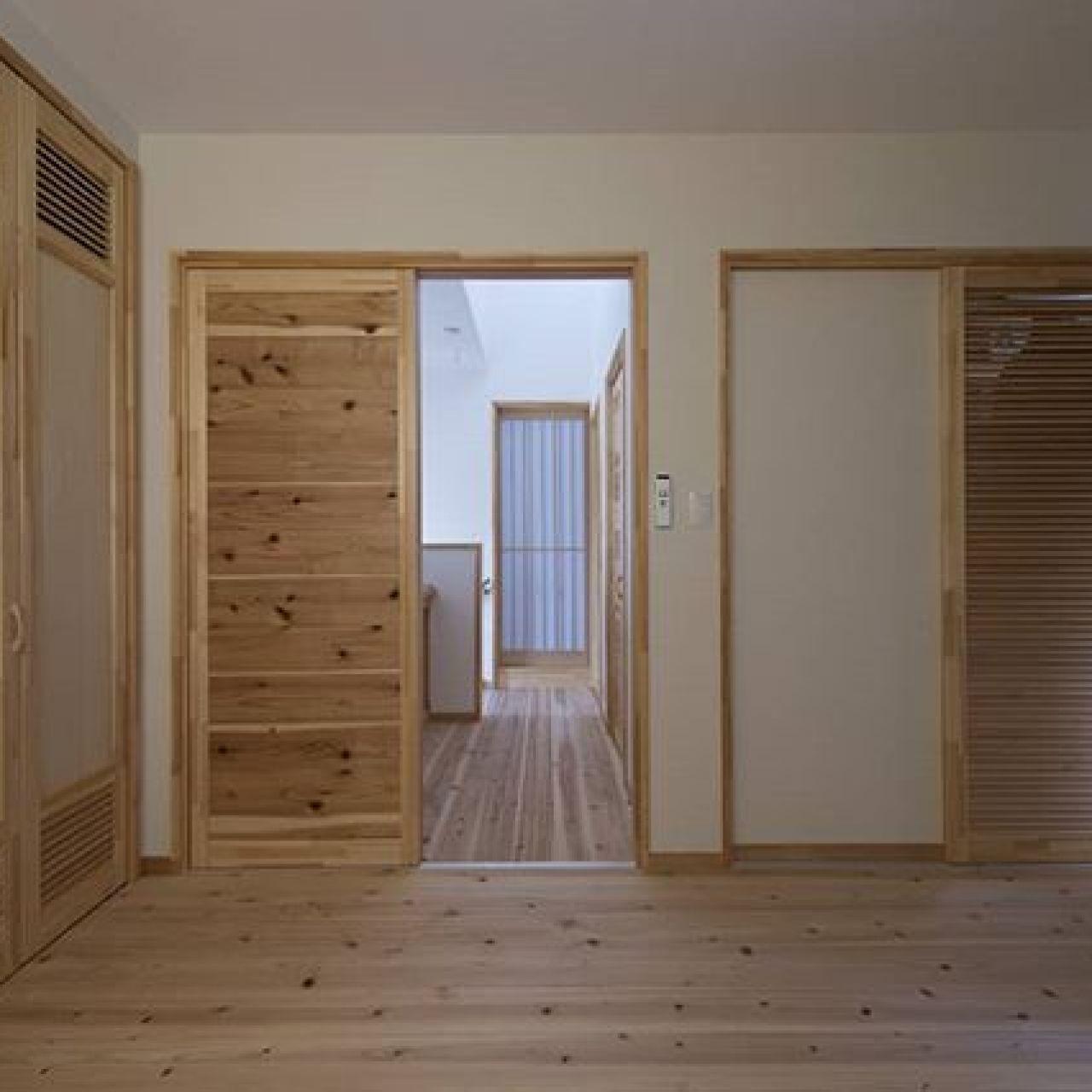 左側がクローゼット、正面右側のドアはファミリークロークへ。どちらも湿気がこもらない通風(ルーバー)建具。杉板の30mmの厚い床は天然の床暖房のように暖かい。奥のホールが明るいのは採光窓のおかげ。#ルーバー #手造り #オリジナル建具 #自然素材の家 #注文住宅#住ま居る #ファミリークローゼット #杉板 #手作り建具 #採光窓 #杉の建具