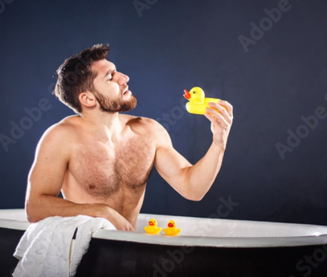 Handsome Naked Muscular Adult Happy Man Taking Bath And Playing With Toy Ducks On Dark