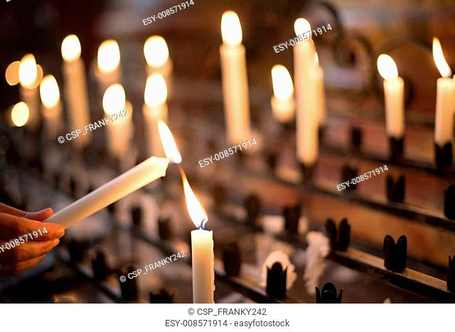 https www agefotostock com age en details photo woman lighting prayer candle esy 008571914