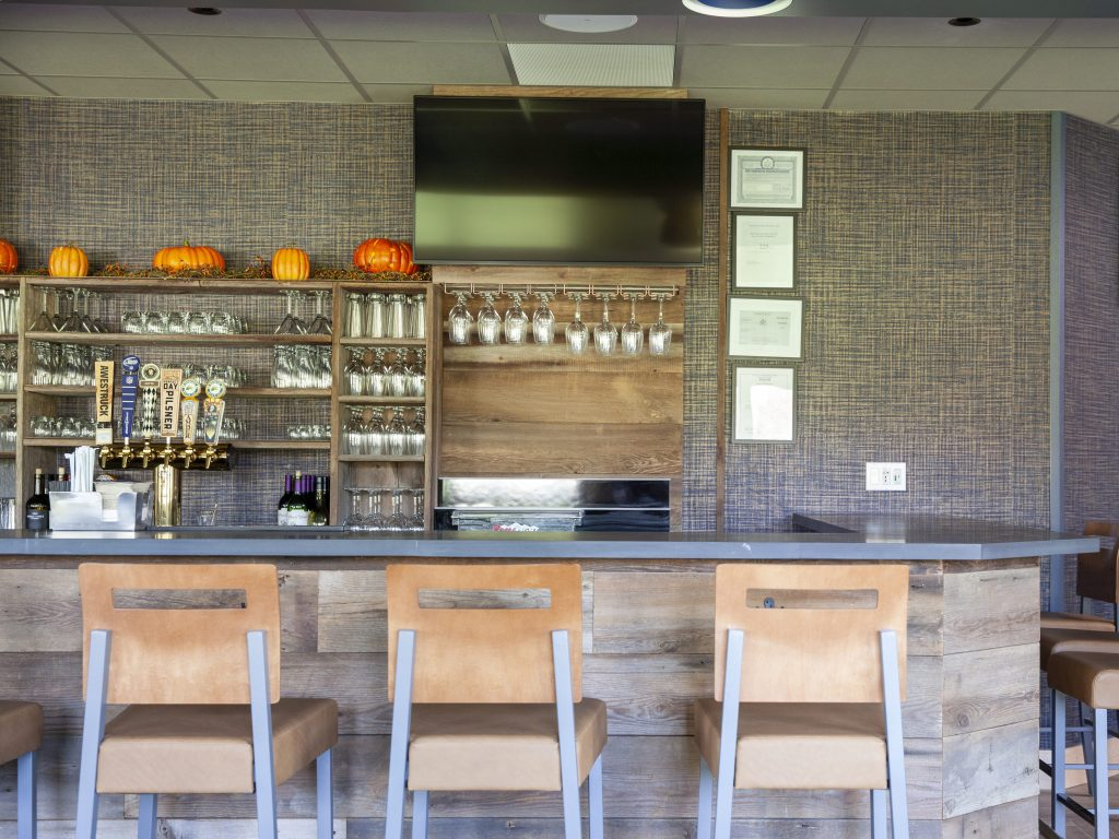 Stone countertop & reclaimed wood shelving & bar front