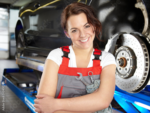 Happy apprentice is proud learning to fix a brake in a garage