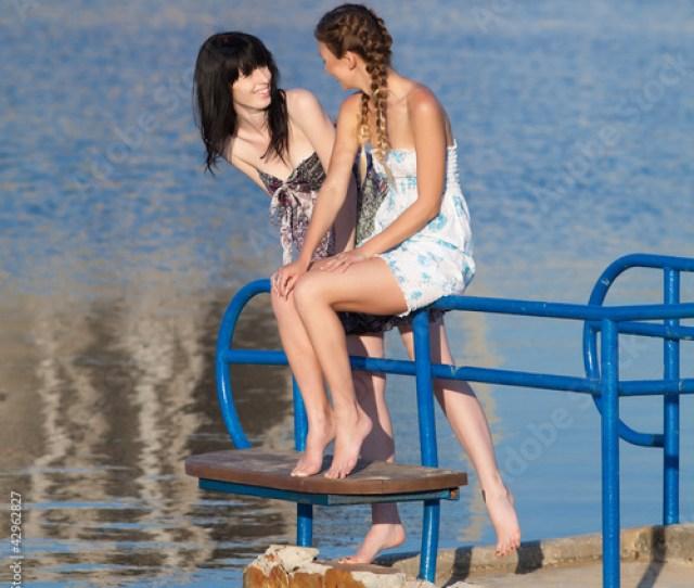 Two Barefoot Girls In Sundresses Talking On Pier