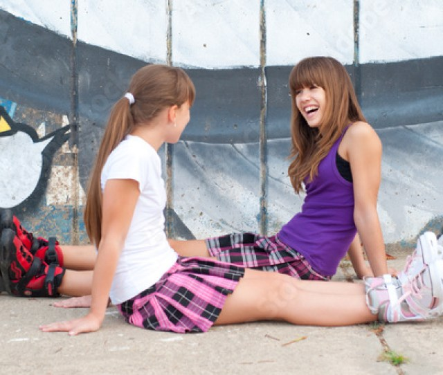 Two Happy Teenage Girls In Roller Skates And Short Skirts