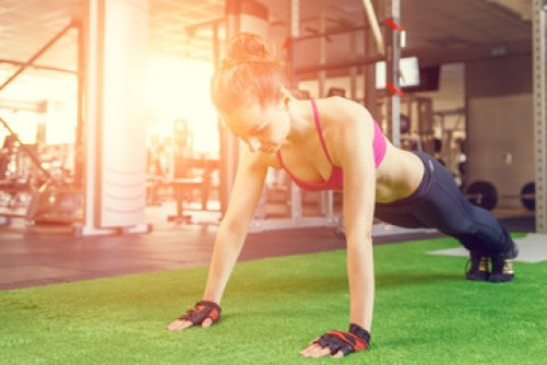 Young athletic woman doing core exercise in gym