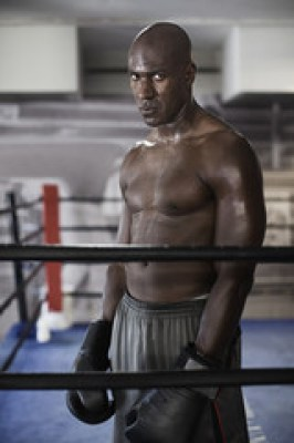Intense African boxer standing in boxing ring