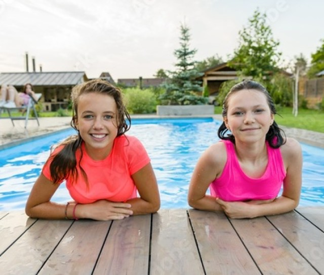 Two Young Teen Girls Having Fun In The Pool Smiling Looking Into The Camera