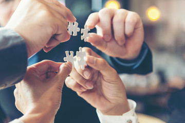 Businessman team work holding two jigsaw connecting couple puzzle piece for matching to goals target, success and start up new project in office, select focus. Business Concept.