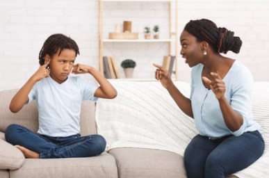 Afro woman lecturing her child who closing ears