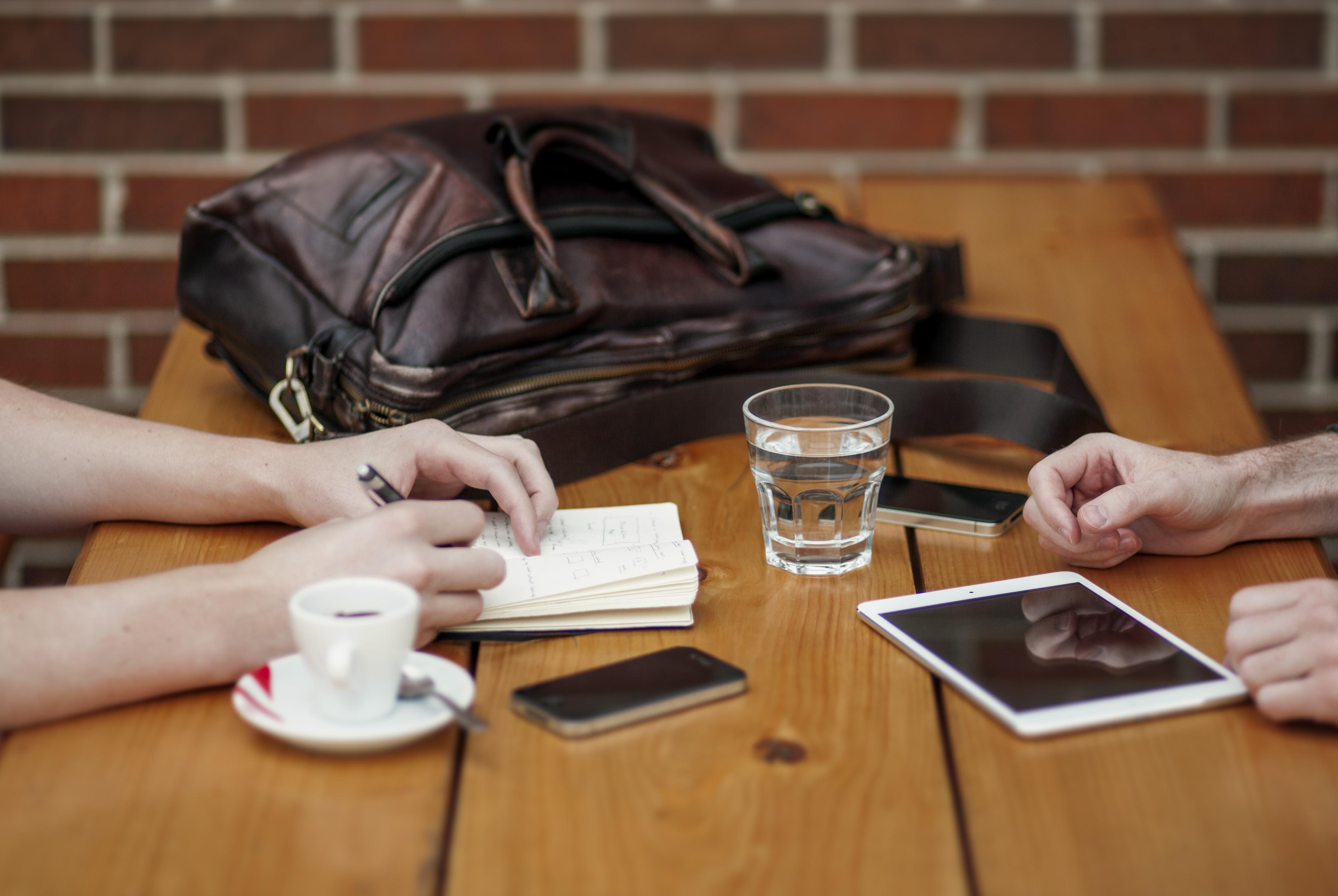 dos personas sentadas delante de la mesa