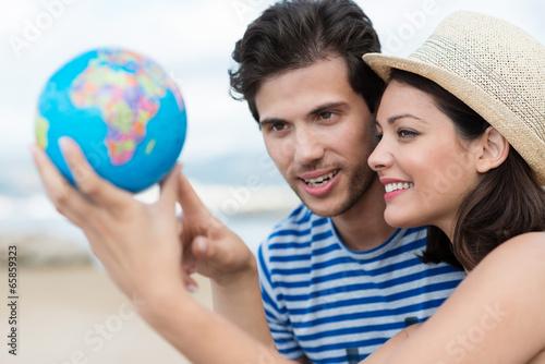 junge leute zeigen auf globus