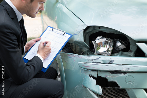 Insurance Agent Examining Car After Accident