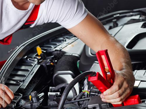 Car mechanic in a garage checks a car