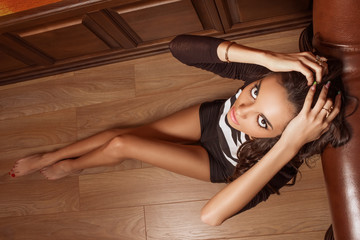 Emotional girl sitting on the wooden floor, clutching his head. Young woman with beautiful face and big eyes. She regretted that he had made, worried, crying.