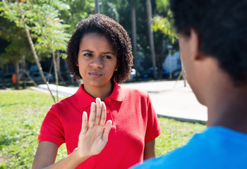 African american woman showing stop sign to man