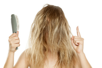 frizz with messy hair, lady holding hair brush and showing finger up at her frizzy hair