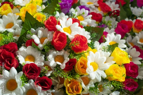 a colorful mixture of different artificial flowers   white daisy     a colorful mixture of different artificial flowers   white daisy  red and  yellow roses