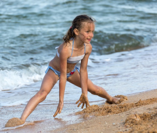 Young Girl Athlete In A Swimsuit At Sea Playing On The Beach On The Sand