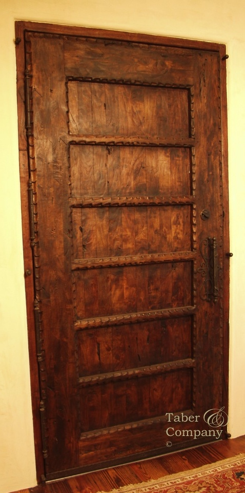 Solid wood door with hand carved mouldings and forged iron