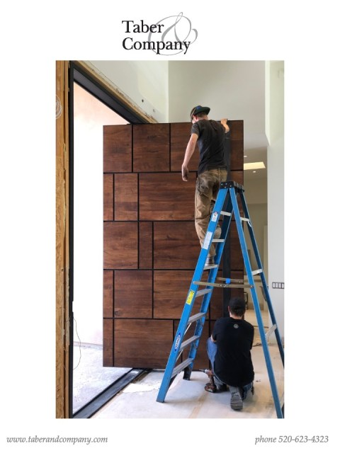 massive wood and iron pivot door for a luxury home.