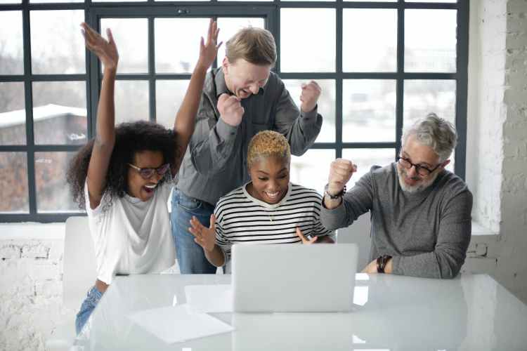 excited multiracial colleagues enjoying triumph together in front of laptop in office