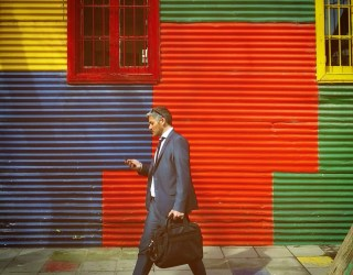 A man in a suit walking in front of a colorful wall in La Boca, Buenos Aires