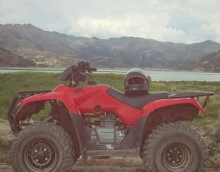 A red quad bike next to a lake