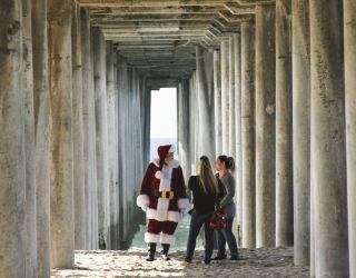 A man dressed as santa claus on a beach