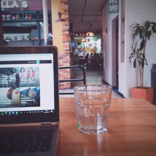 A laptop in a cafe with a glass of water