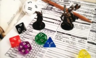D&D minis dice character sheet pencil on rule book