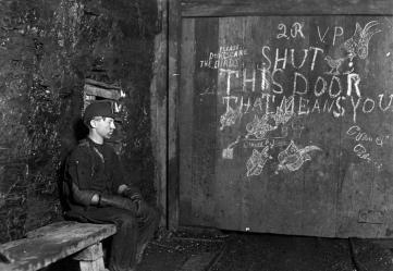 15-year-old Vance, a trapper boy, sits by a large door in West Virginia coal mine in September of 1908. Vance has trapped for several years, receiving 75 cents a day for 10 hours work. All he does is to open and shut this door. Most of the time he sits here idle, waiting for the cars to come. Due to the intense darkness in the mine, the hieroglyphics on the door were not visible until his photo plate was developed.