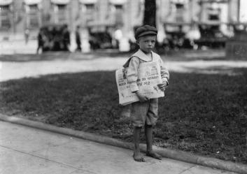 "7-year-old year old Ferris, a small newsboy, or ""newsie"", who did not know enough to make change. Photographed in Mobile, Alabama, in October of 1914. The newspapers he holds are copies of The Mobile Item, with the headline ""Germans Are Driven Out Of Ostend,"" describing the end of the Siege of Antwerp in World War I."