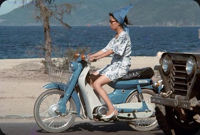 Vẫn là một chiếc xe Yamaha Dame màu xanh dương, nhưng lần này người cầm lái là một thiếu nữ tân thời.