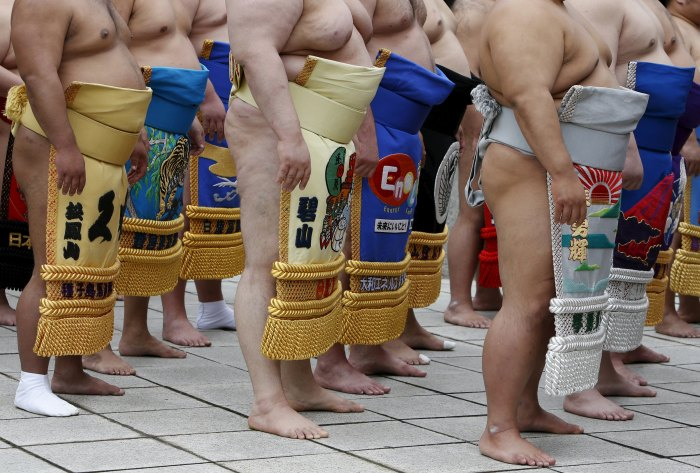Sumo wrestlers line up as they pray before the start of the annual 'Honozumo' ceremonial sumo tournament dedicated to the Yasukuni Shrine in Tokyo, Japan