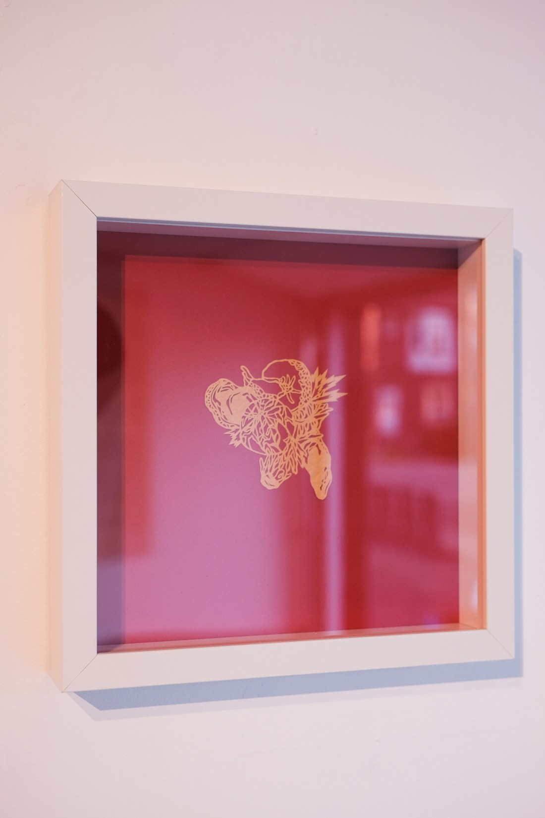 A photo of a small gold papercut of a peeled orange sits in the centre of a red background within a square white frame. The frame is hung on a blank wall.