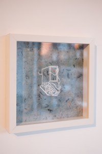 A photo of a small white papercut of a door with a box in front sits in the centre of a blue speckled paper background. It is framed in a square white frame, hung on a blank wall.