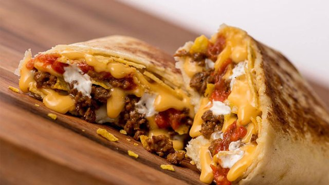 A Stuffed Grilled Taco is cut in half on a cutting board to show the blend of crispy taco shell, ground beef, cheese sauce, hot sauce, sour cream and tortilla chips, all wrapped up in a flour tortilla.