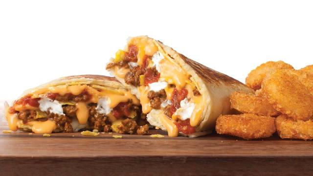 A Stuffed Grilled Taco is divided in half to show a filling of ground beef, melted cheese, sour cream and tomatoes. Some Potato Oles are next to the burrito.