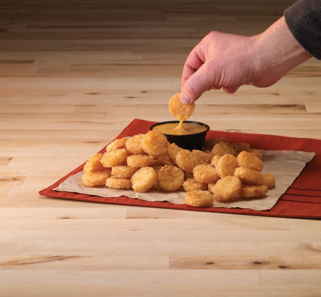 A hand dips a potato disk into a bowl of queso next to a pile of Potato Oles®.