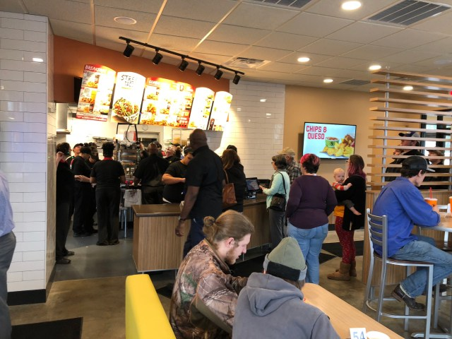 Interior shot of customers and crew members in a crowded store.