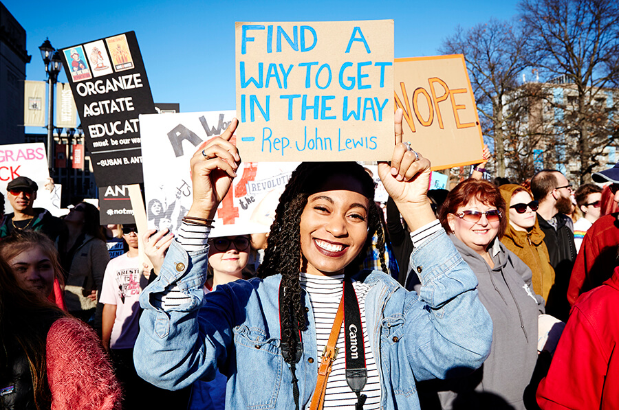 "A woman holds a sign that reads ""Find a way to get in the way - Rep John Lewis"" at the St. Louis Women's March."