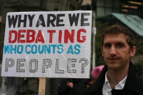 """A person holds a sign reading, """"why are we debating who counts as people?"""""""