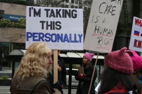 """A person holds a sign that reads """"I'm taking this personally."""""""