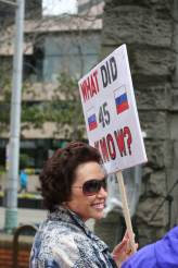 "A person holds a sign that reads, ""what did 45 know?"" with Russian flags on either side of the number 45."
