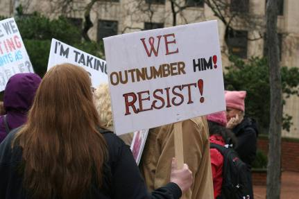 "A person holds a sign that says, ""We Outnumber Him! Resist!"""