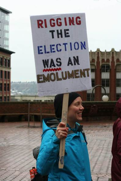 "A person holds a sign that reads, ""rigging the election was an emolument."""