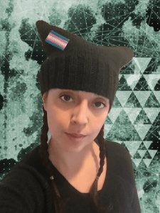 A person wearing a black pussy hat with a trans pride flag.