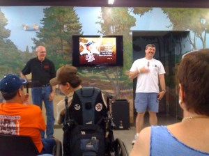 "Neal Brower (standing, left) enjoys watching Allan Newsome do an impromtu Floyd for the audience gathered at in basement theater at the Andy Griffith Museum for Neal's lecture on the ""Back to Nature"" episode on July 12. Photo courtesy of Terry Mayew (Barney chapter)."
