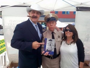 """THE MAN HAS GOT A POINT--Keith Brown of Trivial Trivialties chapter (Pawleys Island, S.C.) points out the new book written by David """"Mayberry Deputy"""" Browning, founder of """"I Ain't No Rockefeller"""" chapter (Bristol, Va.) as they are joined by a happy fan at the recent Westminster festival."""