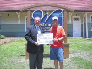 GOOD CAUSE--Tom Rusk (right) of the Mayberry Comes to Westminster festival presents a check for $500 to Sheriff Mike Crenshaw of Oconee County, S.C., in support of drug education programs in local schools.