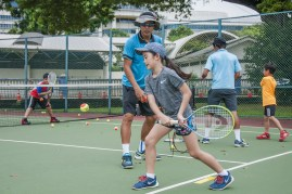 Junior Tennis Camp with coach teaching child how to swing a racquet by TAG International Tennis Academy